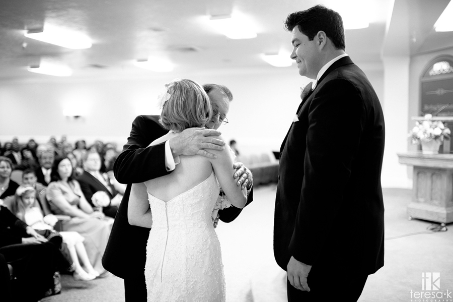 father hugs little girl goodbye at wedding ceremony