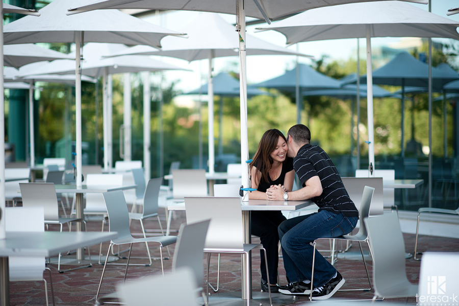 Cute picture of couple interacting under an umbrella at the CalStrs building