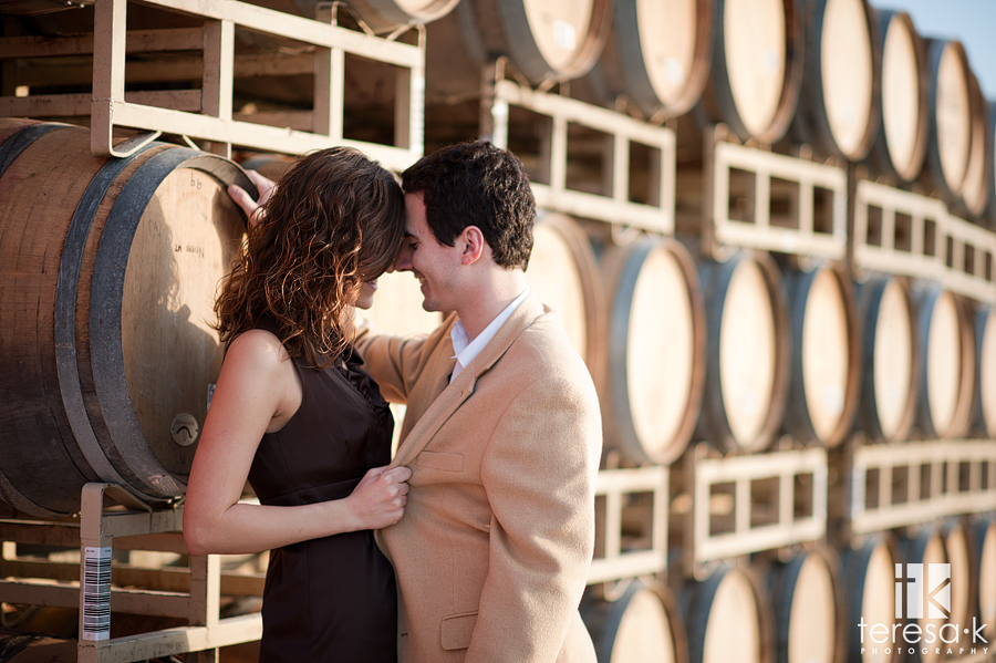bride and groom kissing by wine barrels