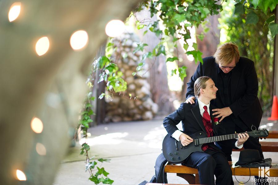 bride's son plays guitar at wedding