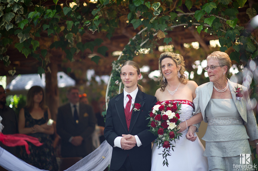 bride coming down aisle with mom and son