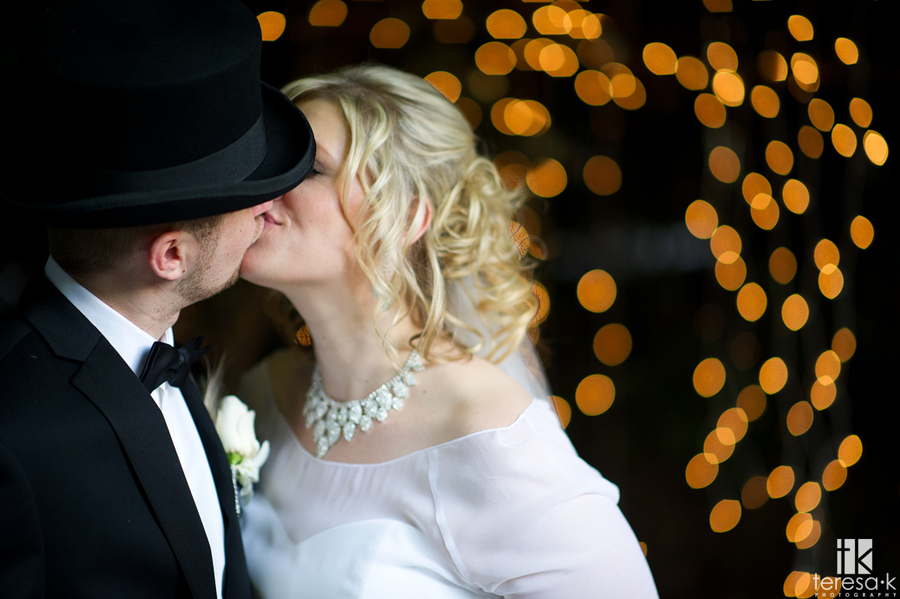 bride and groom kiss in front of lights