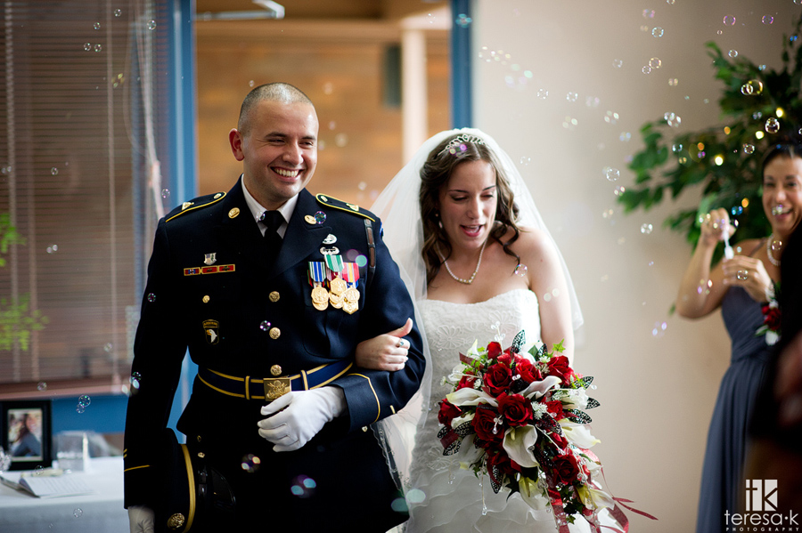 army groom and bride walk into bubbles at reception